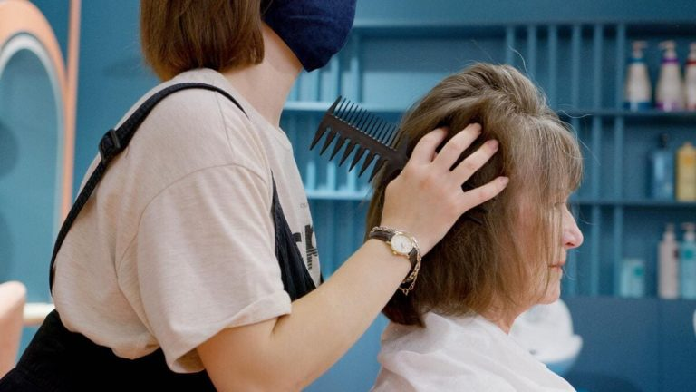 femme se fait brosser les cheveux chez le coiffeur