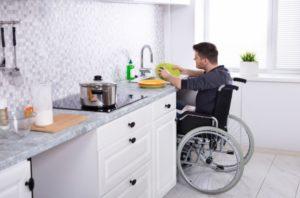 Homme en fauteuil roulant fait la vaisselle