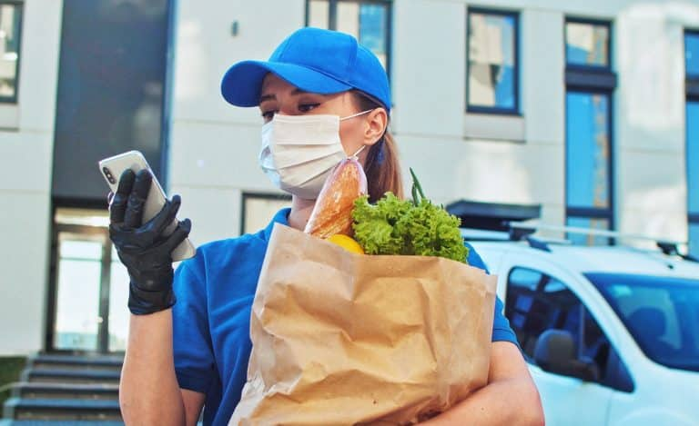Close up of the caucasian attractive young women worker of the supermarket delivery typing on the